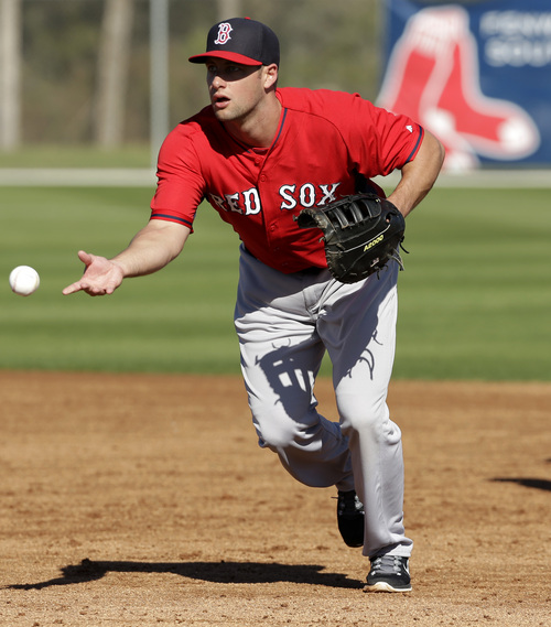 Boston Red Sox right fielder Alex Hassan fields the ball during spring training baseball practice, Monday, Feb. 17, 2014, in Fort Myers, Fla. (AP Photo/Steven Senne)