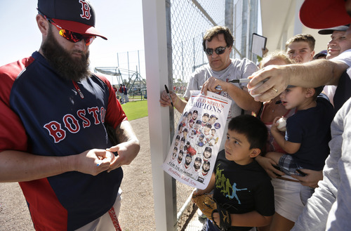 Boston Red Sox first baseman Mike Napoli, left, signs autographs for fans during spring training baseball practice, Monday, Feb. 17, 2014, in Fort Myers, Fla. (AP Photo/Steven Senne)