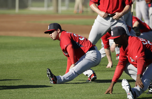 Boston Red Sox relief pitcher Junichi Tazawa, left, stretches during spring training baseball practice, Monday, Feb. 17, 2014, in Fort Myers, Fla. (AP Photo/Steven Senne)
