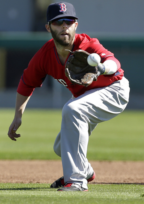 Boston Red Sox second baseman Dustin Pedroia fields a ball during spring training baseball practice, Monday, Feb. 17, 2014, in Fort Myers, Fla. (AP Photo/Steven Senne)