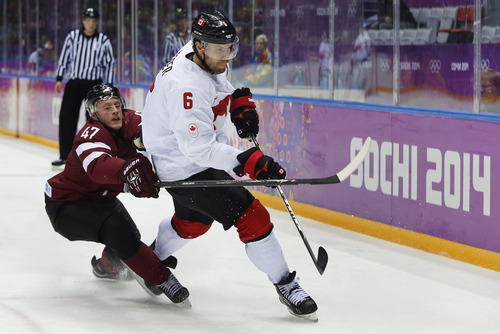 Latvia forward Martins Cipulis reaches around Canada defenseman Shea Weber during the second period of a men's quarterfinal ice hockey game at the 2014 Winter Olympics, Wednesday, Feb. 19, 2014, in Sochi, Russia. (AP Photo/Julio Cortez)
