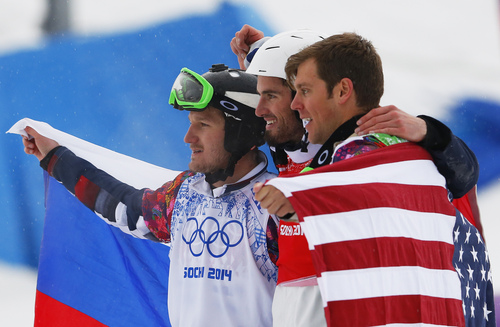 France's Pierre Vaultier, center, celebrates his gold medal with silver medalist Nikolai Olyunin of Russia, left, and bronze medalist Alex Deibold, right, of the United States after the men's snowboard cross final at the Rosa Khutor Extreme Park, at the 2014 Winter Olympics, Tuesday, Feb. 18, 2014, in Krasnaya Polyana, Russia.(AP Photo/Sergei Grits)
