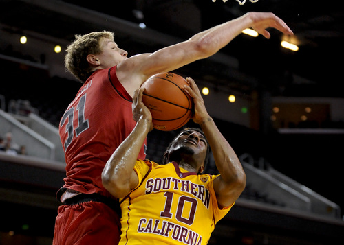 Utah center Dallin Bachynski (31) attempts to block Southern California guard Pe'Shon Howard (10) as he goes up for a shot during the second half of an NCAA college basketball game, Thursday, Feb. 13, 2014, in Los Angeles. Utah won 79-71. (AP Photo/Gus Ruelas)