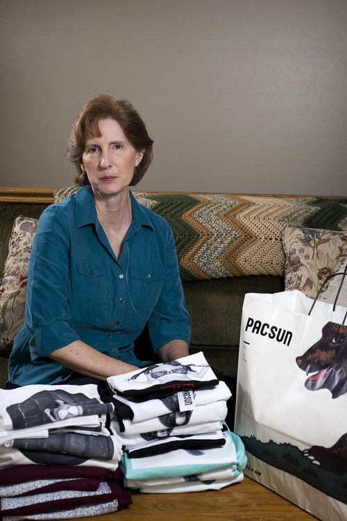 Judy Cox sits for a portrait next to a stack of T-shirts with what she believes are pornographic designs Monday, Feb. 17, 2014, in Orem, Utah. Cox purchased the entire stock of T-shirts for $567 from the PacSun store in Orem believing their display broke Orem's decency code. Cox said she complained about the window display to a store manager and was told the T-shirts couldn't be taken down without approval from the corporate office. (AP Photo/The Daily Herald, Mark Johnston)