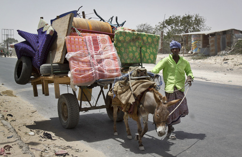 A Somali man walks alongside a donkey cart laden with his belongings as he flees from the Heliwa district in the north of the capital Mogadishu, Somalia Thursday, Feb. 20, 2014. Residents in Mogadishu say that hundreds of families are fleeing the Somali capital after a spike in the number of clashes between militants and pro-government troops, with dozens of vehicles piled high with belongings headed to the outskirts of Mogadishu on Thursday. (AP Photo/Farah Abdi Warsameh)