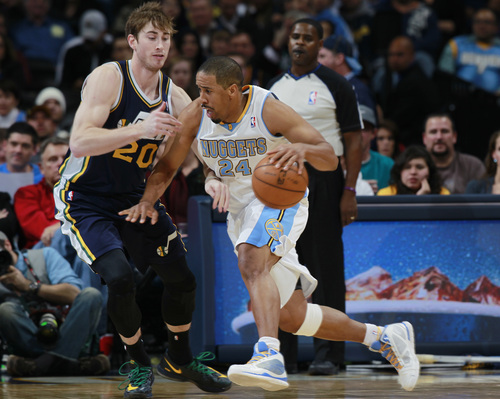 FILE - Denver Nuggets guard Andre Miller, right, works ball inside as Utah Jazz guard Gordon Hayward covers in the fourth quarter of Utah's 103-93 victory in an NBA basketball game in Denver on Friday, Dec. 13, 2013. The Nuggets on Thursday traded Miller, a former University of Utah standout, to the Washington Wizards. (AP Photo/David Zalubowski)
