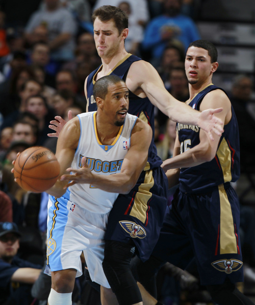 FILE - Denver Nuggets guard Andre Miller, front, passes the ball as New Orleans Pelicans forward Jason Smith, center, and guard Austin Rivers cover in the third quarter of the Nuggets' 102-93 victory in an NBA basketball game in Denver on Sunday, Dec. 15, 2013.The Nuggets on Thursday traded Miller, a former University of Utah standout, to the Washington Wizards. (AP Photo/David Zalubowski)
