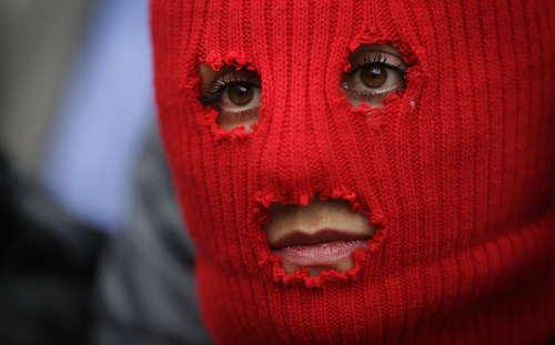 A member of the Pussy Riot punk group - who have feuded with Vladmir Putin's government for years - looks on during a press conference, Thursday, Feb. 20, 2014, in Sochi, Russia. (AP Photo/David Goldman)