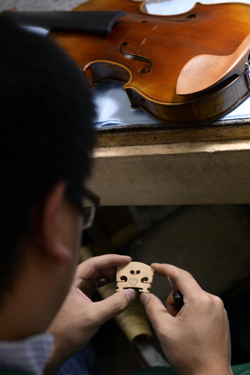 Francisco Kjolseth  |  The Salt Lake Tribune Lious Chang creates a new bridge made from maple at Charles W Liu Fine Violins in Midvale recently. Liu has been making fine violins for years and hosts the Stradivarius International Violin Competition. From a small space at 7450 South State that used to be a house, Liu has built a business that caters to those just starting out, to the most gifted professional.