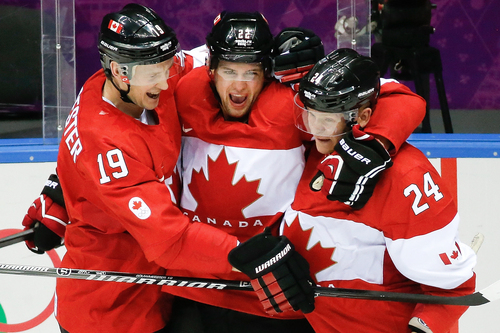 Canada forward Benn Jamie, center, celebrates his goal against the USA with teammates Jay Bouwmeester, left, and Corey Perry, right, during the second period of the men's semifinal ice hockey game at the 2014 Winter Olympics, Friday, Feb. 21, 2014, in Sochi, Russia. (AP Photo/Mark Humphrey)