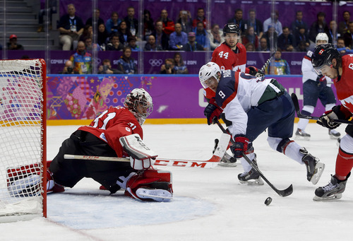 Canada goaltender Carey Price blocks a shot by USA forward Zach Parise during the second period of a men's semifinal ice hockey game at the 2014 Winter Olympics, Friday, Feb. 21, 2014, in Sochi, Russia. (AP Photo/Petr David Josek)