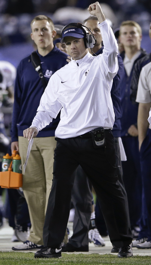 Utah State coach Matt Wells gives his approval after his team scored against Northern Illinois during the first half of the Poinsettia Bowl NCAA college football game Thursday, Dec. 26, 2013, in San Diego. (AP Photo/Lenny Ignelzi)