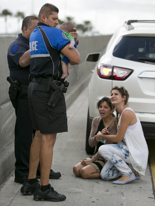 Sweetwater officer Amauris Bastidas helps rescue a five-month-old baby boy, Sebastian de la Cruz,  who stopped breathing. At center, the baby's aunt, Pamela Rauseo, 37, performed CPR after pulling her SUV over on the side of the road along the west bound lane on Florida state road 836 just east of 57th Avenue around 2:30pm on Thursday, Feb. 20, 2014.  At right is Lucila Godoy who stopped her car to assist in the rescue. (AP Photo/Miami Herald, Al Diaz)