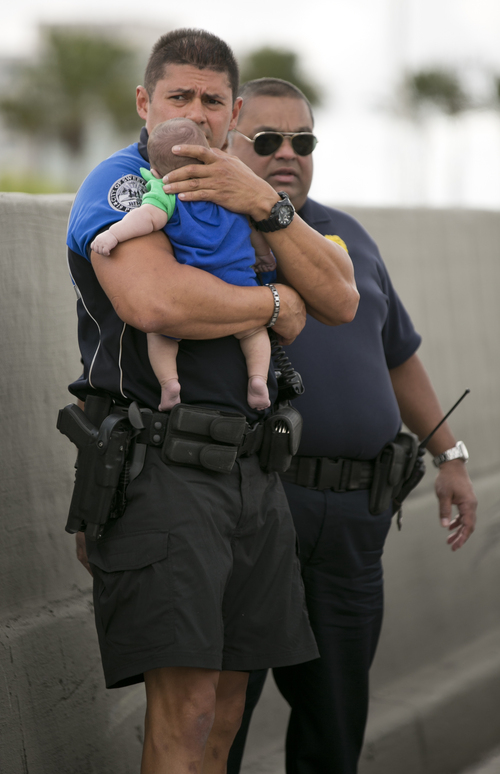Sweetwater officer Amauris Bastidas keeps a watchful eye waiting for paramedics after aiding a five-month-old Sebastian de la Cruz who stopped breathing. The baby's aunt performed CPR after pulling her SUV over on the side of the road along the west bound lane on Florida state road 836 just east of 57th Avenue around 2:30 pm on Thursday, Feb. 20, 2014. (AP Photo/Miami Herald, Al Diaz)