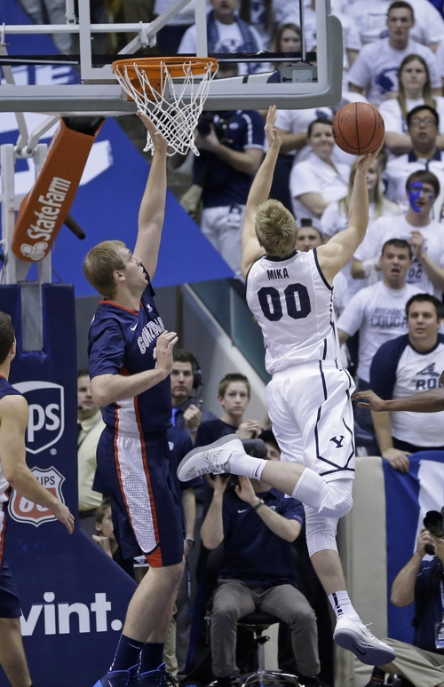 Brigham Young's Eric Mika (00) shoots as Gonzaga's Przemek Karnowski (24), of Poland, defends in the first half of an NCAA college basketball game, Thursday, Feb. 20, 2014, in Provo, Utah. (AP Photo/Rick Bowmer)