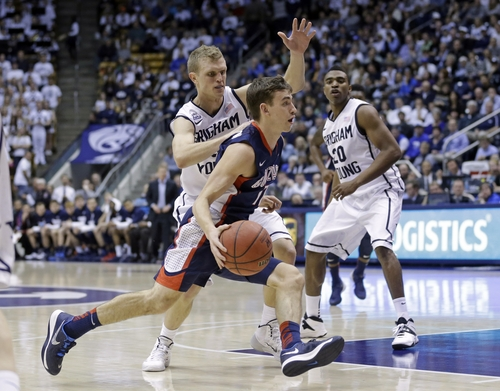 Gonzaga's David Stockton, center, drives to the basket as Brigham Young's Tyler Haws, left, defends as teammate Anson Winder (20) looks on in the first half of an NCAA college basketball game, Thursday, Feb. 20, 2014, in Provo, Utah. (AP Photo/Rick Bowmer)