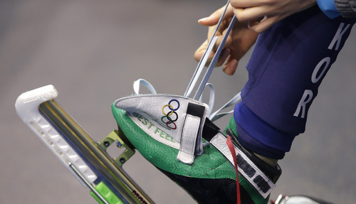 Shim Suk-Hee of South Korea laces up before competing in a women's 1000m short track speedskating semifinal at the Iceberg Skating Palace during the 2014 Winter Olympics, Friday, Feb. 21, 2014, in Sochi, Russia. (AP Photo/Darron Cummings)