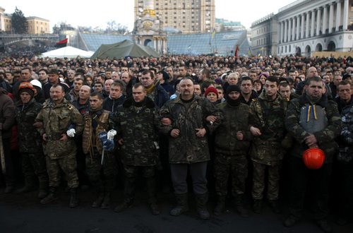 People gather at Independence Square during a funeral procession for anti-government protesters killed in clashes with the police in Kiev, Ukraine, Friday, Feb. 21, 2014. In a day that could significantly shift Ukraine's political destiny, opposition leaders signed a deal Friday with the country's beleaguered president that calls for early elections, a new constitution and a new unity government. (AP Photo/ Marko Drobnjakovic)