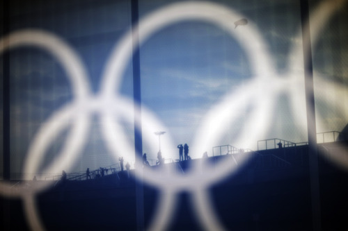 Spectators are seen through a screen with the Olympic rings on a security fence as they take a photo on the steps of the Bolshoy Ice Dome at the 2014 Winter Olympics, Friday, Feb. 21, 2014, in Sochi, Russia. (AP Photo/David Goldman)