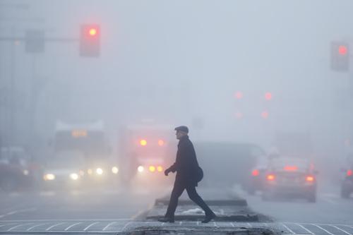 A man crosses North Broad Street through dense fog, Friday, Feb. 21, 2014, in Philadelphia. (AP Photo/Matt Rourke)