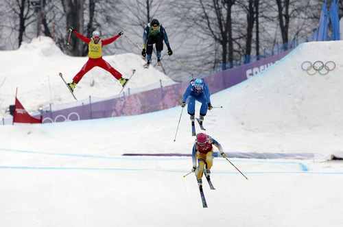 Competitors in the women's ski cross small final, from left, Switzerland's Fanny Smith, Australia's Katya Crema, Austria's Katrin Ofner, and Sweden's Sandra Naeslund take the final jump at the Rosa Khutor Extreme Park, at the 2014 Winter Olympics, Friday, Feb. 21, 2014, in Krasnaya Polyana, Russia. (AP Photo/Andy Wong)