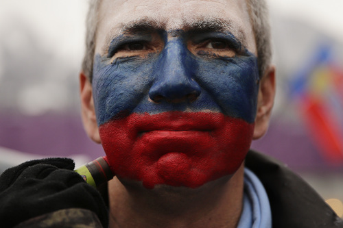Kamil Aizetulin gets his face painted in the colors of the Russian flag during a women's ski cross seeding run at the Rosa Khutor Extreme Park, the 2014 Winter Olympics, Friday, Feb. 21, 2014, in Krasnaya Polyana, Russia. (AP Photo/Jae C. Hong)