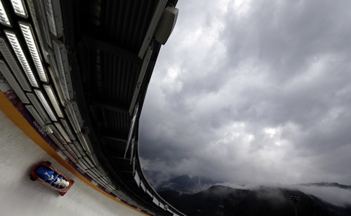 The team from Italy ITA-1, piloted by Simone Bertazzo, take a curve during the men's four-man bobsled training at the 2014 Winter Olympics, Friday, Feb. 21, 2014, in Krasnaya Polyana, Russia. (AP Photo/Natacha Pisarenko)