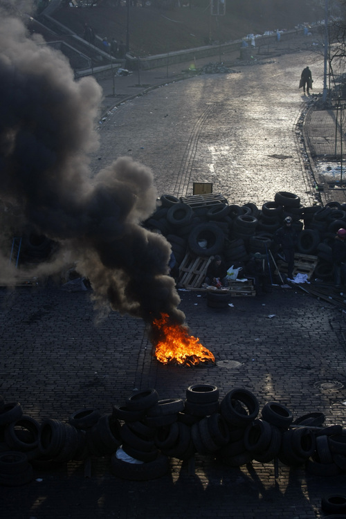 A fire burns on a barricade at Independence Square in Kiev, Ukraine, Friday, Feb. 21, 2014. Ukraine's presidency said Friday that it has negotiated a deal intended to end battles between police and protesters that have killed scores and injured hundreds, but European mediators involved in the talks wouldn't confirm a breakthrough. (AP Photo/ Marko Drobnjakovic)