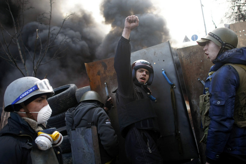 """Anti-government protesters shout """"Glory to the Ukraine"""" as they man a barricade at Independence Square in Kiev, Ukraine, Friday, Feb. 21, 2014. Ukraine's presidency said Friday that it has negotiated a deal intended to end battles between police and protesters that have killed scores and injured hundreds, but European mediators involved in the talks wouldn't confirm a breakthrough. (AP Photo/ Marko Drobnjakovic)"""