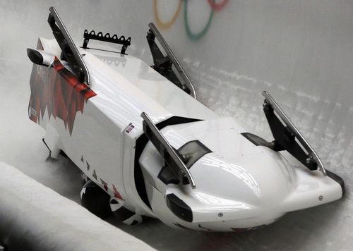 The team from Canada CAN-3, with Justin Kripps, Jesse Lumsden, Cody Sorensen and Ben Coakwell, slide down the track upside down after crashing in turn sixteen during the men's four-man bobsled competition at the 2014 Winter Olympics, Saturday, Feb. 22, 2014, in Krasnaya Polyana, Russia. (AP Photo/Dita Alangkara)