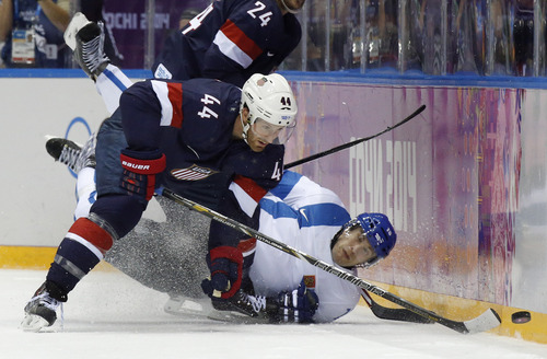 Finland forward Tuomo Ruutu hits the ice as he challenges USA defenseman Brooks Orpik for the puck during the second period of the men's bronze medal ice hockey game at the 2014 Winter Olympics, Saturday, Feb. 22, 2014, in Sochi, Russia. (AP Photo/Mark Humphrey)