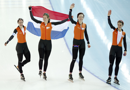 Marrit Leenstra, Lotte van Beek, Jorien ter Mors, and Ireen Wust of the Netherlands celebrate with the national flag after taking the gold medal on the women's team pursuit at the Adler Arena Skating Center at the 2014 Winter Olympics, Saturday, Feb. 22, 2014, in Sochi, Russia. (AP Photo/Pavel Golovkin)