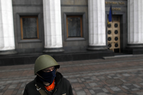 An anti-government protester stands guard in front of Ukraine's parliament in Kiev, Ukraine, Saturday, Feb. 22, 2014. Fears that Ukraine could split in two mounted Saturday as regional lawmakers in the pro-Russian east questioned the authority of the national parliament. Protesters took control of Ukraine's capital and parliament sought to oust the president. (AP Photo/ Marko Drobnjakovic)