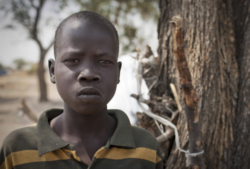In this photo taken Saturday, Feb. 15, 2014, Ajing Abiik, 12, who fled from his hometown of Bor when the fighting broke out in December, stands next to the tree where he and his two brothers sleep in Minkaman IDP camp, Awerial County, in South Sudan. The fighting in the world's newest country has left thousands of its youngest citizens either orphans or separated from their parents, increasing their vulnerability to sickness, malnutrition and recruitment by warring groups as child soldiers. (AP Photo/Mackenzie Knowles-Coursin)