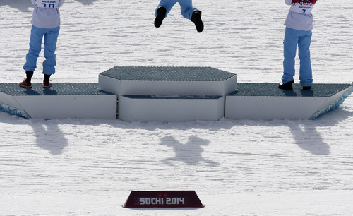Norway's Marit Bjoergen casts as shadow as she celebrates winning the gold during the flower ceremony of the women's 30K cross-country race at the 2014 Winter Olympics, Saturday, Feb. 22, 2014, in Krasnaya Polyana, Russia. (AP Photo/Dmitry Lovetsky)