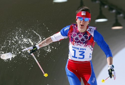 Czech Republic's Eva Vrabcova-Nyvltova throws a bottle of water as she skis during the women's 30K cross-country race at the 2014 Winter Olympics, Saturday, Feb. 22, 2014, in Krasnaya Polyana, Russia. (AP Photo/Dmitry Lovetsky)