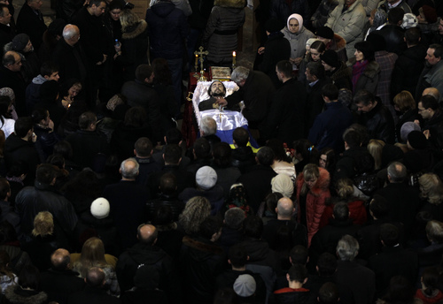 An open casket with the body of Bogdan Solchunuk, 28, lays in the centre of St. Paul and Peter church, during his funeral service in Lviv, western Ukraine, Saturday, Feb. 22, 2014. Church services were held Saturday in the pro-opposition stronghold of Lviv in the west of Ukraine for the locals who were killed in Kiev during the past week. Lviv activists say 19 of their people were killed in the violence at Maidan. (AP Photo/Darko Vojinovic)