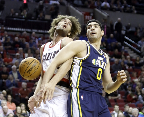 Portland Trail Blazers center Robin Lopez, left, and Utah Jazz center Enes Kanter battle for a rebound during the first half of an NBA basketball game in Portland, Ore., Friday, Feb. 21, 2014. (AP Photo/Don Ryan)