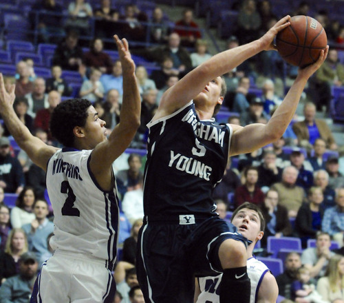 BYU's Kyle Collingsworth (5) shoots against Portland's Alec Wintering (2) during an NCAA college basketball game in Portland, Ore., Thursday Jan. 23, 2014. (AP Photo/Greg Wahl-Stephens)