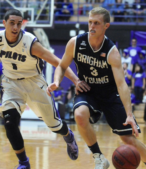 BYU's Tyler Haws (3) drives against Portland's Bryce Pressley (1) during the first half of an NCAA college basketball game in Portland, Ore., Thursday Jan. 23, 2014. (AP Photo/Greg Wahl-Stephens)
