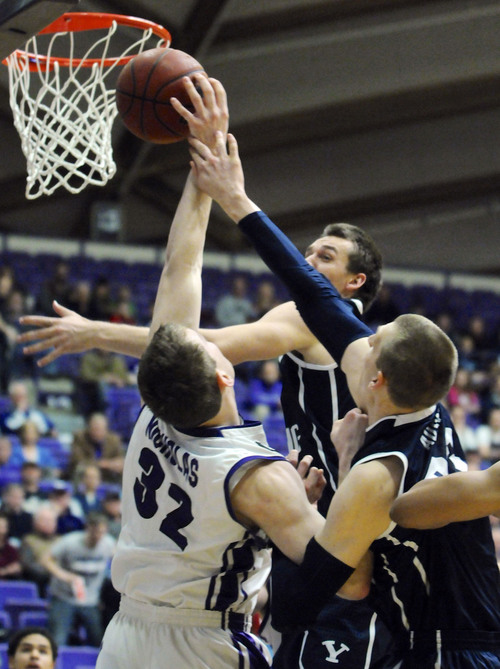 BYU's Kyle Collingsworth (5) shoots against Portland's Ryan Nicolas (32) during the first half of an NCAA college basketball game in Portland, Ore., Thursday Jan. 23, 2014. (AP Photo/Greg Wahl-Stephens)