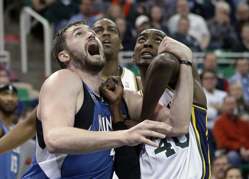 Minnesota Timberwolves' Kevin Love, left, battle with Utah Jazz's Jeremy Evans (40) under the boards as Utah Jazz's Alec Burks, center, looks on in the second half of an NBA basketball game Saturday Feb. 22, 2014, in Salt Lake City. The Timberwolves won 121-104. (AP Photo/Rick Bowmer)