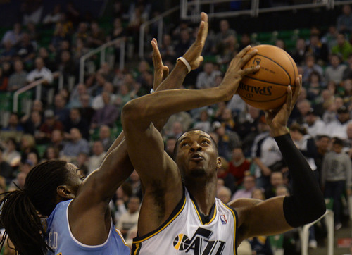 Rick Egan  | The Salt Lake Tribune   Utah Jazz power forward Derrick Favors (15) looks for a shot over Denver Nuggets power forward Kenneth Faried (35), in NBA action, Utah Jazz Vs.The Denver Nugget's, inSalt Lake City, Monday, January 13, 2014.