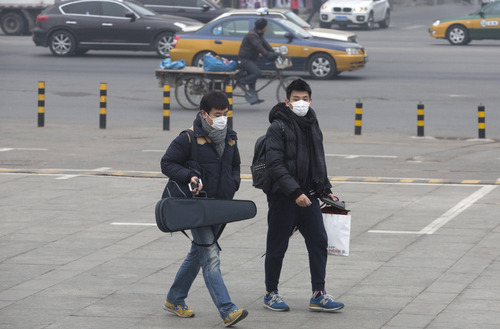 Men wearing masks walk near a road during a day of heavy pollution in Beijing, China, Sunday, Feb. 23, 2014. (AP Photo/Ng Han Guan)