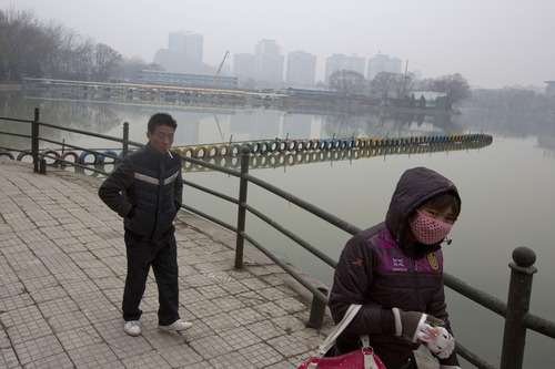 Residents walk around a lake during a day of heavy pollution in Beijing, China, Sunday, Feb. 23, 2014. (AP Photo/Ng Han Guan)