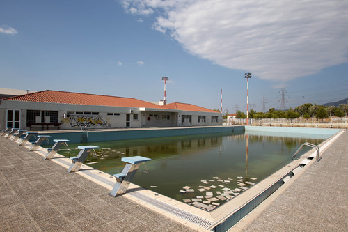 FILE - In this Thursday, Aug. 2, 2012, file photo, murky water and rubbish fill an abandoned training pool for athletes at the Olympic village on the northern fringes of Athens. The legacy of Athens' Olympics has stirred vigorous debate, and Greek authorities have been widely criticized for not having a post-Games plan for the infrastructure. While some of the venues built specifically for the games have been converted for other uses, many are underused or abandoned, and very few provide the state with any revenue. Some critics even say that the multibillion dollar cost of the games played a modest role in the nation's 2008 economic meltdown.(AP Photo/Thanassis Stavrakis, File)