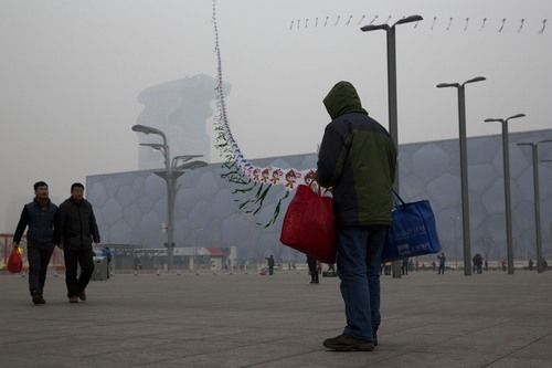 In this picture taken Sunday, Feb. 23, 2014, a street vendor flies kites printed with the Beijing Olympic games mascot image near the Water Cube aquatic center in Beijing, China. The Water Cube _ where U.S. swimmer Michael Phelps made history by winning eight gold medals _ has been transformed into a water park popular among local families. Its operators even peddle purified glacier water under the Water Cube brand for additional income. Beijing, which spent more than $2 billion to build 31 venues for the 2008 Summer Games, is reaping some income and tourism benefits from two flagship venues, though many sites need government subsidies to meet hefty operation and maintenance costs. (AP Photo/Ng Han Guan)