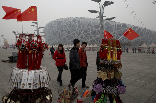 In this picture taken, Sunday, Feb. 23, 2014, tourists pass by memorabilia on sale near the iconic Bird's Nest National Stadium in Beijing, China. The National Stadium, nicknamed the Bird's Nest because of its lattice design, has become a key Beijing landmark and a favored backdrop for visitors' snapshots. But few tourists are willing to pay more than $8 to tour the facility as enthusiasm for the 2008 Games fades, and the venue has struggled to fill its space with events. Beijing, which spent more than $2 billion to build 31 venues for the 2008 Summer Games, is reaping some income and tourism benefits from two flagship venues, though many sites need government subsidies to meet hefty operation and maintenance costs. (AP Photo/Ng Han Guan)