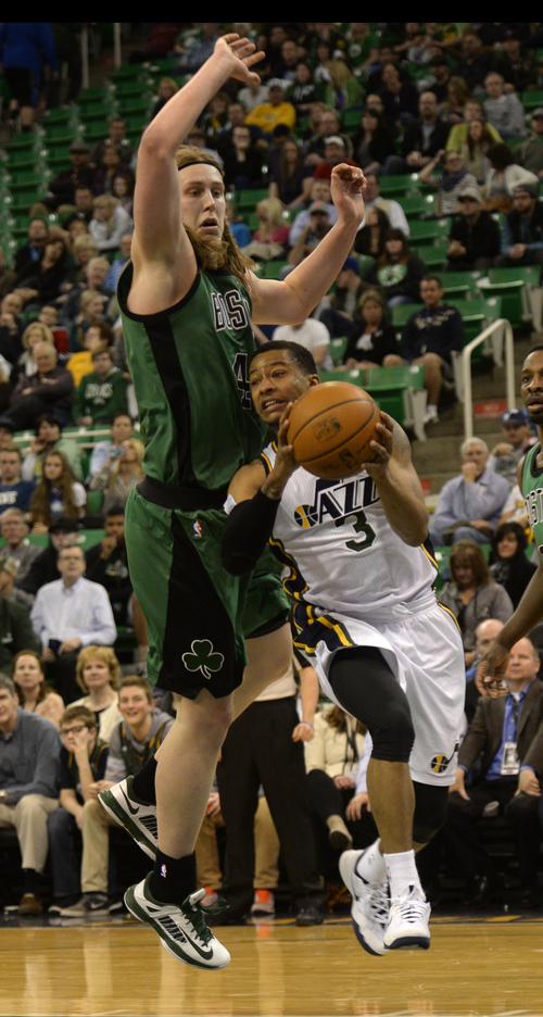 Rick Egan  | The Salt Lake Tribune   Utah Jazz point guard Trey Burke (3) drove under the hoop past Boston Celtics center Kelly Olynyk (41), in NBA action, at the EnergySolutions Arena, Monday, February 24, 2014.