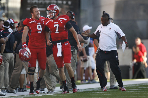 Scott Sommerdorf   |  The Salt Lake Tribune Utah LB Trevor Reilly, #9, congratulates QB Travis Wilson after Wilson's 3 yard TD pass to Dres Anderson as  Utah took a quick 7-0 lead over USU early in the 1st period, Thursday, August 29, 2013. Utah co-OC Brian Johnson does a dance at right to celebrate.
